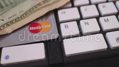 Macro dolly rotate over keyboard with one credit card and $10 U.S. bill    Trademarked logos are included as part of an editorially illustrative theme, suggesting concepts such as e-commerce and online purchasing.