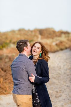 an engaged couple posing for a photo in ireland red hair with black dress with flowers and red nail varnish and green earrings Engagement Couple, Engagement Shoots, Couple Posing, Couple Photos, Ireland Beach, Flower Dresses, Red Hair, I Am Awesome, Wedding Day