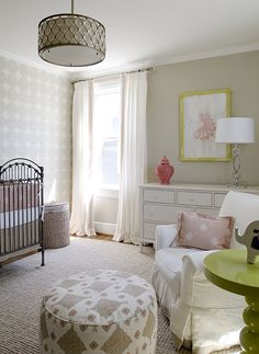 Sweet pink  tan baby girl's nursery with tan walls paint color, antique crib, pink  gray crib bedding, ivory  silver gray circles wallpaper, white curtains window panels with coral pink Greek key trim, jute rug, white glider with pink ruffled pillow, glossy green lacquer spindle table, white chest, coral pierced carthage lantern, gray  pink pouf, yellow  pink art and beehive drum pendant.