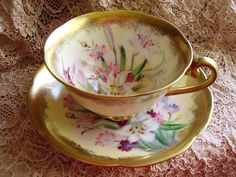 Beautifully hand painted tea cup and saucer  with gold trim and gorgeous flowers designed  inside the cup and across the saucer.  Tea cup is 4 in