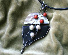 Elegance - šungit, perleť Autorský cínovaný šperk ze šungitu velikosti 5 x 3,5 x 0,6 cm a plátku perleti. Šperk je doplněn říčními perlami a pravými červenými korály. Celý šperk má míry 9,5 cm na výšku a 4 cm na šířku, měřeno v nejširších místech. Šperk je velmi elegantní a mnohem hezčí ve skutečnosti než na foto - perleť ani sametově černý ...