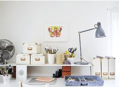 Storage boxes, a lamp and trays on a desk.