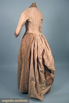 SILK BROCADE BUSTLE DRESS, 1880s 1-piece, allover small floral in cream, pink, & gold, w/ gold satin & colorful brocade ribbon trim, carved & gilt MOP buttons in stylized horseshoe design.