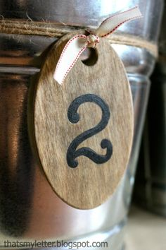wooden stenciled numbers on galvanized buckets hung with twine.