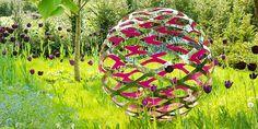 Modern stainless steel sculpture in a beautiful garden setting