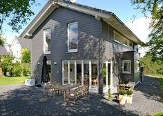 Ein dänisches Ehepaar verwirklichte sich seinen Traum im Rheinland. Eine Außenfassade im dunklen Grau, weiße Fenster und Türen, viel Licht und naturbelassenes...