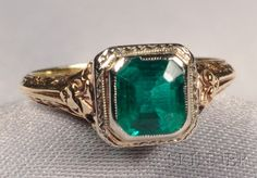 Art Deco 14kt Bicolor Gold and Emerald Ring, bezel-set with an emerald-cut emerald measuring approx. 6.30 x 5.70 x 3.95 mm, open gallery, engraved accent
