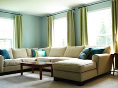 LOVE the blue walls with green curtains in this living room.  Love the sectional too.