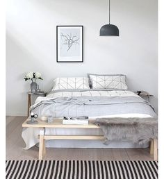 Une banquette en bois dans une chambre grise et blanche