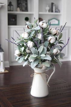 White metal pitchers are very popular in farmhouse decor. Add some cotton, lambs ear and lavender and you add even more rustic charm. The silver, blue/green tones in the lambs ear, complements the lavender and cotton beautifully. Ive finished the piece off with moss and tied jut around
