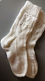 This is a very pretty sock with heart motifs done in lace. I have made a quirky chart. I am sorry I don't have a program to create charts so I use a sort of spread sheet. I make it as simple and clear as I can and I explain the one complex stitch that is used. I used one skein of Stroll yarn for the sock and it hits me about mid-calf. I have big feet (size 9) so if you make a smaller one (shorter foot) you will need less yarn, of course. You could also make this a shorter cuff by only doing…