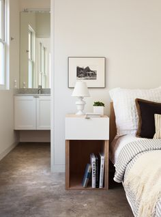 narrow bedside table Bedroom Transitional with bed bedding concrete floor guest…