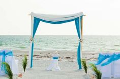 Turquoise and white chiffon decorate the two post arch with an aisle of grasses .. chic!