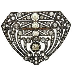 A 14k gold and silver brooch set with a combination of rose cut and old mine cut diamonds. The largest center old mine cut diamond is approx. 0.80ct. and pearls ranging in diameter from 3.7mm to 5mm.