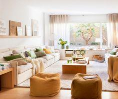 15_Salón con amplio sofá, pufs en tonos camel y marrón, estante con cuadros y cojines verdes y amarillos_00426437