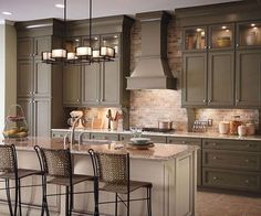 I really like how great the olive colored cabinets look with the brick backsplash. Image from Decorating Files.