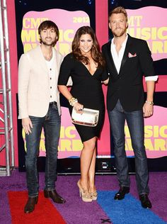"""Lady Antebellum was very monochromatic for their big night at the 2012 CMT Music Awards. While their lead lady Hillary Scott went for a simple form-fitting LBD with a white clutch, her bandmates Dave Haywood and Charles Kelley (Katherine Heigl's brother-in-law) opted for blue jeans paired with white and black blazers respectively. The trio took home the award for group video of the year (""""We Owned the Night)."""