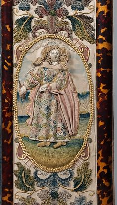 The figure of Jael was worked separately and attached over an under drawing. The face and arms are made with silk satin, her headscarf and cloak are detached needle-lace stitch worked on a wire which could be shaped to create a billowing effect. The skirt is worked entirely on wire of a heavier gauge. Embroidered mirror frame. 1672. British. Silk, metal, glass beads, mica, seed pearls.