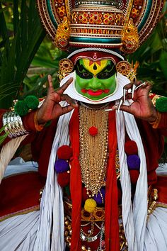 Portrait of Kathakali dancer in full make-up and costume portraying Pacha, wearing elaborate headgear called Mudis and demonstrating the double hand movement known as Samyutha Mudras