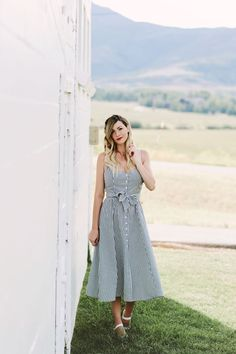 Caitlin Lindquist of Dash of Darling styles a stripe button down reformation dress that is the perfect feminine summer outfit  for the fourth of july.