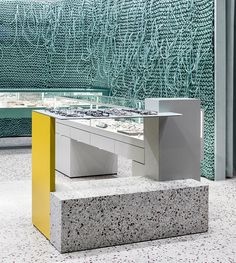 a muted background of grey walls and terrazzo flooring provide a blank canvas for the splashes of bright colors to energize the space.