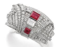 DIAMOND AND SYNTHETIC RUBY BRACELET, 1930S. Of geometric design, set with step-, carré-, circular-cut and baguette diamonds, accented with step-cut synthetic rubies, length approximately 200mm, signed Marc, French assay and maker's marks, the centre detachable and may be worn as a clip.