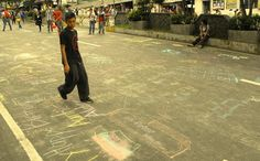 A young boy walks over the doodles and chalk drawings on the pavements of Session Road in Baguio City.