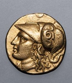 Ancient Greek gold coin stamped with Athena, who wears a helmet.