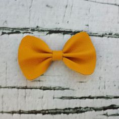 "This is a hand-cut leather bow available on an alligator clip or elastic headband.Please leave in notes at checkout your color preference for the elastic headband. Refer to ""Policies"" and ""Reviews"" pages for more information."