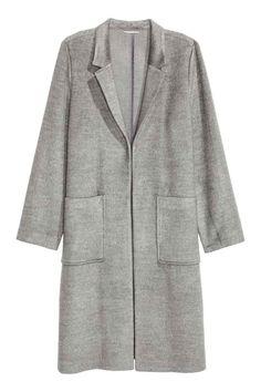 Manteau feutré: Manteau de longueur genou en doux tissu feutré avec petits revers. Modèle avec poches plaquées devant et fente sur les côtés. Sans boutonnage. Non doublé.