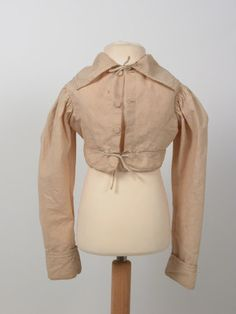 Jacket; Spencer - Unbleached calico, decorated with large chain stitch in silk thread. Long sleeves with turned back cuffs. Wide pointed collar. Possibly boys. 1815 (circa)