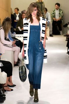 A denim jumpsuit overlayed with a cozy black and white striped vest is nautical chic for the city, complete with those Rykiel stripes on socks, paired with sandals. It's concurrently sexy and sweet, a contradiction the French woman has mastered. Imaxtree  - HarpersBAZAAR.com