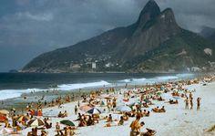 Saudades do Rio - UOL Fotoblog DOMINGO DE PRAIA  Esta foto é do arquivo da LIFE, não tendo sido publicada na revista.  Vemos as praias de Ipanema e do Leblon em 1957, quando a Favela do Vidigal, um dos locais mais privilegiados do Rio, ainda tinha pequenas dimensões. Ainda era um tempo em que todos se sentavam no chão, sem cadeiras de praia (no máximo uma toalha ou uma esteira), sem muitos ambulantes e sem as horríveis tendas para vendas de bebidas nas areias.
