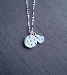 """A handcrafted fine silver (.999%) moon pendant paired with a genuine moonstone charm.Hangs on a sterling silver 16"""" chain.($36)"""