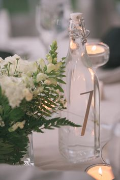 water bottle table numbers, photo by Katie Slater http://ruffledblog.com/romantic-connecticut-wedding #tablenumbers #wedding #weddingideas