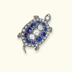 AN ANTIQUE SAPPHIRE AND DIAMOND BROOCH - Christie's auction 2009 -Modelled as a tortoise, the shell pavé-set with cushion-cut sapphires and old-cut diamonds to the diamond-set tail, feet and head with ruby eyes, mounted in silver and gold, circa 1880, 4.0 cm wide
