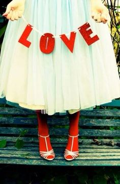 Girl holding love sign made with red letters