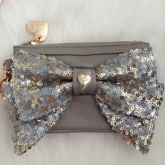 """BANANA SALEBetsey Johnson Oh Bow Sequined Case So cute and on trend! Top zipper closure. Exterior features sequined bow accent. Interior features ID slot. Gold tone clip. 3.5""""H X 5.5""""W. Stone colored leather. No Trades. TB1009. Betsey Johnson Bags Wallets"""