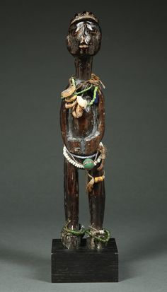 Important Standing Shrine Figure. Kulango Tribe, Côte d'Ivoire, 19th century, 1850-1890. This is an extremely rare and beautiful antique standing shrine figure from the Kulango peoples of Côte d'Ivoire, with significant evidence of use in a shrine context. The figure has an abstract impressionist quality, with an offset, disarming pose, with with its head poised atop an elongated neck and arms clasped at belly.