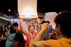 PHOTO: Couple launches paper lantern during Thailand's Yi Peng celebration for good luck