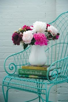 Beautiful blooms atop a turquoise chair.