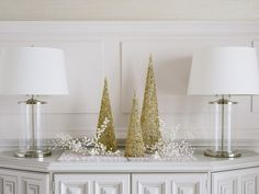 When decorating spaces for holiday entertaining, it's important to consider individual areas within a single space to ensure a cohesive look. Carry the tone-on-tone look to surrounding sideboards, buffets and bars. Here, a serving buffet is lightly decorated with metallic and glass accents in the same off-white and champagne tones seen on the dining table.