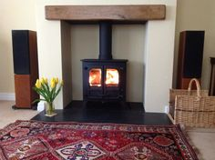 Charnwood Island 1 on honed granite hearth, painted recess and oak fireplace beam.