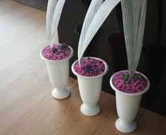 Grouped vases with flower en masse at base and strong architectural leaves by FLOWERS BY BORNAY CLOSER