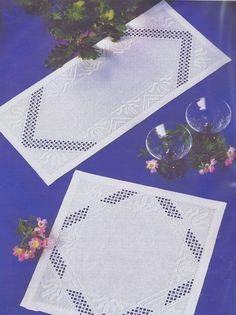 A crisp white mat with openwork sections and fleur de lys motifs.