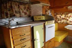 The kitchen of our 1957 Westerner travel trailer. Original curtains, upholstery and appliances.