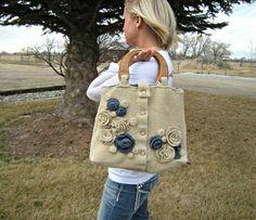 Dit is een 100% upcycled wol handtas gemaakt van een beige trui-vest. De bloemen zijn blauw en bruin Gevilte wol. De voering is blauw, bruin en wit geruite stof met zakken. Paren goed met een denim rok of blue jeans en een t-shirt. Houten handvatten en knop sluiting.  breedte openstelling 12 breedte onder 14 x 4 hoogte 11