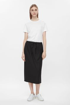 A classic shape with inspiration from sportswear, this pencil skirt is made from lightweight unlined wool with a drawstring waist. Designed to slip-on, it has in-seam pockets and a back slit.