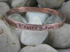 """Copper Bangle - Faith Hope Love  This gorgeous copper bangle is hand stamped all the way around with """"faith, hope, love"""". Looks great alone or stacked with our other bangles."""