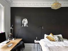 2 SCHWARZ LIEBT WEISS   Schwarz und Weiss sind ein starkes Paar, das sich gegenseitig guttut. Wagen Sie es, eine Wand schwarz zu streichen, der Effekt kann sich sehen lassen. Hier ist dies in einem Schlafzimmer geschehen. Der Boden, die Stuckaturen, die Sockelleisten und die Bettwäsche sind weiss, ein grosses Schwarzweissfoto kokettiert und verbindet die starken Kontraste. (Bild: Blueberry Home)